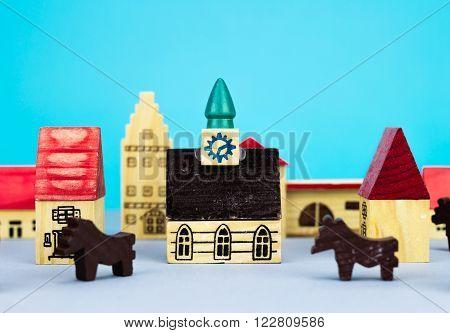 Figurine wooden hometown buildings on blue background