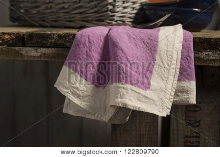 Purple Dinner Napkin Dangling From Edge Of Wooden Table