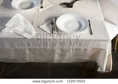 Sets Of Dinnerware And Crumpled Napkin On White Linen-covered Table