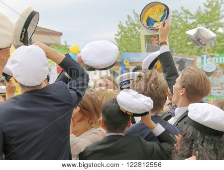 STOCKHOLM SWEDEN - JUN 10 2015: Group of happy teenagers raising the graduation cap celebrating the graduation after finishing high school at the school Globala gymnasiet June 10 2015 Stockholm Sweden