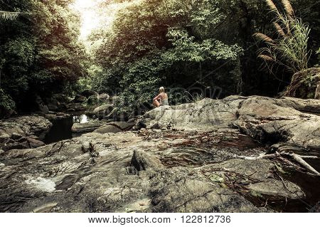 Tranquil scene with meditating young woman enjoying the pristine beauty of nature in the tropical rainforest at the waterfall  during sunset far away from the urban  bustle. Rays of light breaking through the dense foliage