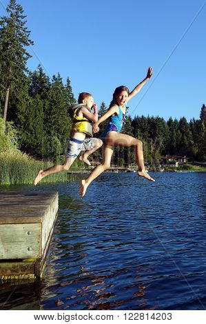 Boy and girl jumping from floating dock in St.Mary lake on Salt Spring Island,BC,Canada.
