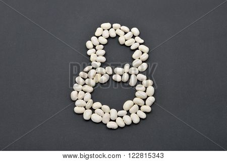Number eight made from white beans on black background. Food vegan, vegetarian. Healthy food
