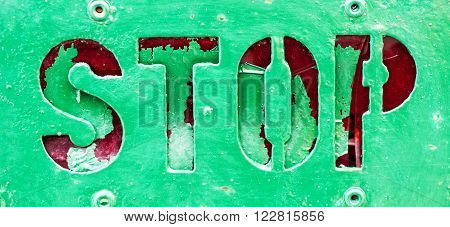 Grunge green painted metal Stop sign with paint overflowing into the red indented letters and four rivets