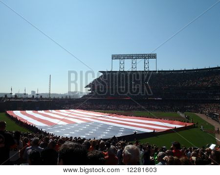 Large Usa Flag Held Across The Outfield  By A Line Of People During National Anthem