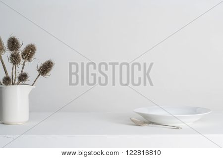 Dinner Plate And Vase With Thistles On A White Countertop