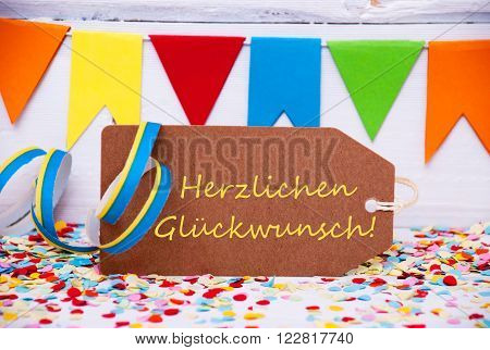 Label With German Text Herzlichen Glueckwunsch Means Congratulations. Party Decoration Like Streamer, Confetti And Bunting Flags. White Wooden Background With Vintage, Retro Or Rustic Syle