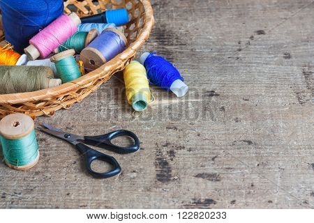 Bobbins with thread and scissors. Sewing tools on the old wooden surface. Vintage background