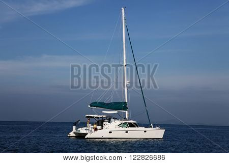 Small white yaht in blue ocean