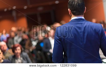 Speaker giving a talk on corporate Business Conference. Audience at the conference hall. Business and Entrepreneurship event. ** Note: Visible grain at 100%, best at smaller sizes