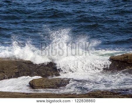 Ocean waves splash over rocks on Maine's coast near Pemaquid Point.