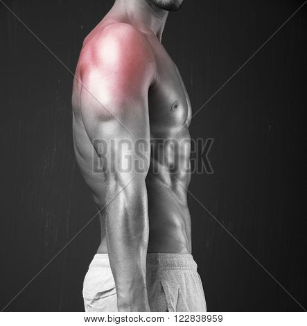 Muscular young man with inflamed shoulder on dark background