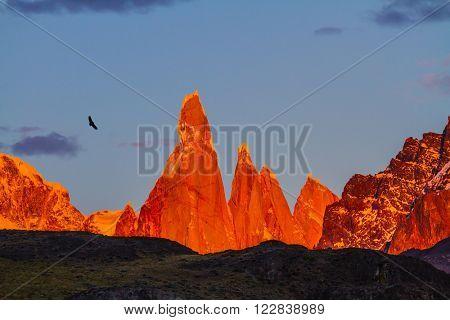 Fantastic Patagonia. The crimson sunset illuminates the top of impressive cliffs Fitz Roy