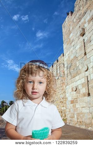 Cute little boy with long blond curls and blue eyes in knitted skullcap. He stands at fortress walls of Old City of Jerusalem. The Jewish holiday of Sukkot