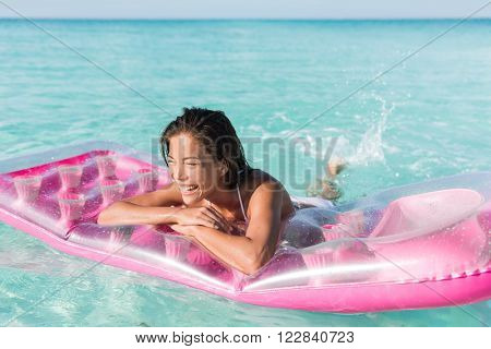 Beach girl having fun splashing water in ocean floating on pink pool float toy air mattress. Asian woman relaxing in the sun swimming in the perfect turquoise sea at holiday resort.