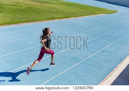 Runner sprinting towards success on run path running athletic track. Goal achievement concept. Female athlete sprinter doing a fast sprint for competition on blue lane at an outdoor field stadium. poster