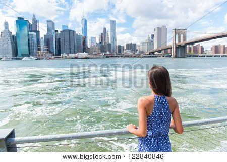 New York city urban woman enjoying view of downtown Manhattan skyline from Brooklyn park living a happy lifestyle walking during summer travel in USA. Female Asian tourist in her 20s.