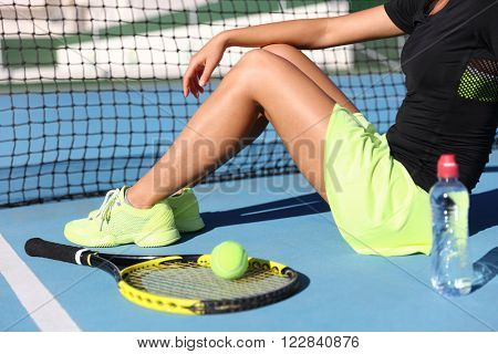 Lower body closeup of tennis player woman resting sitting on outdoor court showing tennis racket / racquet, ball and water bottle wearing yellow sportswear outfit. Sports shoes and skirt.