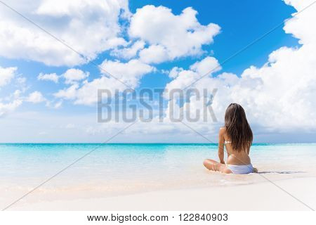 Beach vacation dream woman enjoying summer holiday on dreamy perfect ocean tropical destination. Person sitting from the back alone on deserted white sand beach getaway.