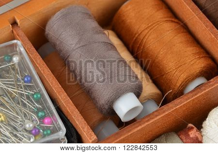 Sewing kit from threads and pin in wooden box
