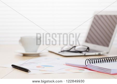 Office workplace with with laptop and coffee on wooden desk table in front of window with blinds. Focus on pen