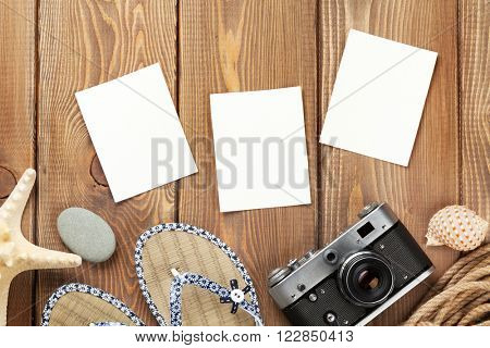 Travel and vacation photo frames and items on wooden table. Top view poster
