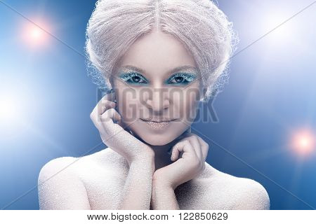 Beautiful young female face with bright fashion snow make-up.