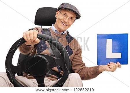 Cheerful senior gentleman holding an L-sign seated on a car seat isolated on white background