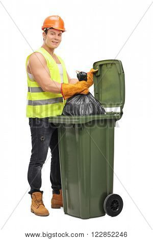 Full length portrait of a young male waste collector emptying a garbage bin isolated on white background