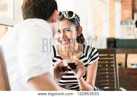 Asian couple, Indonesian woman and Korean man, in cafe flirting while drinking coffee, barista in the background