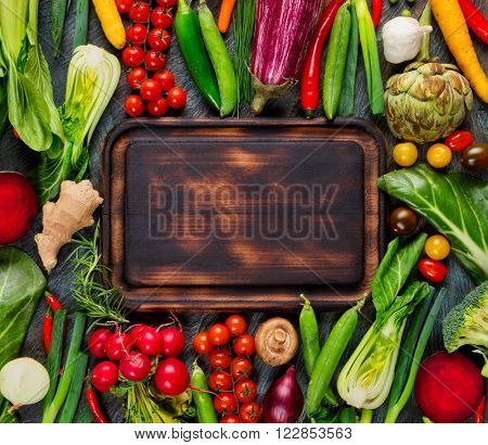 Collection of fresh vegetables placed on black stone with breadboard