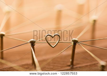 Linking entities. Network, networking, social media, internet communication abstract. Online love or matching. Web of gold wires, with one connection having a heart.