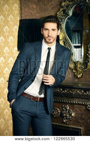 Respectable young man standing by a fireplace in a room with classic interior. Luxury. Men's beauty, fashion. poster