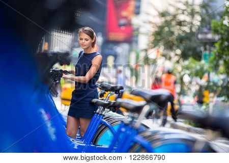 City bike rental/sharing/pooling - woman taking public city bicycle (color toned image; shallow DOF)