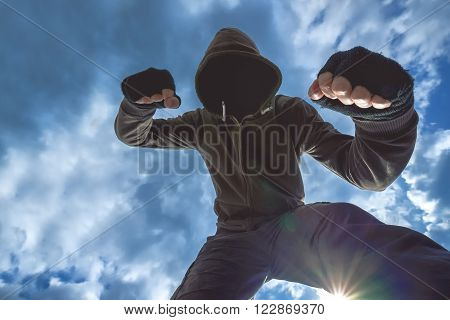 Violent attack unrecognizable hooded male criminal kicking and punching victim on the street.