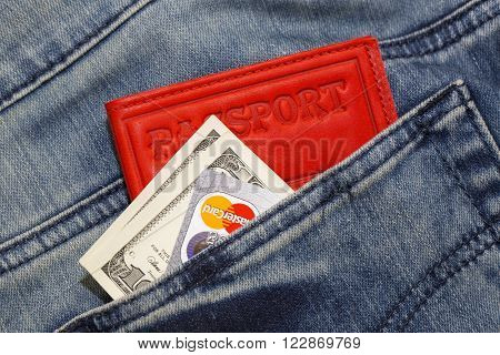 KHARKIV, UKRAINE - MARCH 16, 2016: American dollars, passport, credit cards  Mastercard sticking out of the pocket of jeans