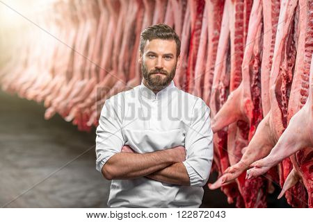 Portrait of a handsome butcher in white uniform at the meat manufacturing with pork carcasses on the background