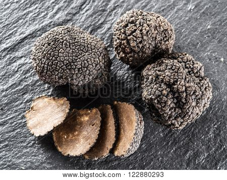 Black truffles and truffle slices on the graphite board.