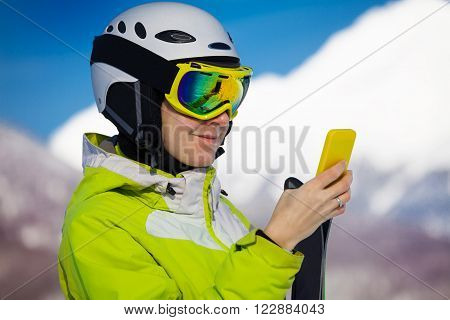 Close portrait of a woman texting with phone wearing ski mask with mountain peaks on background
