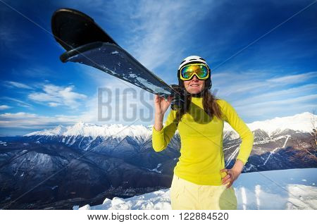 Close front wide angle portrait of woman in light winter clothes holding ski standing on top of skiing mountains