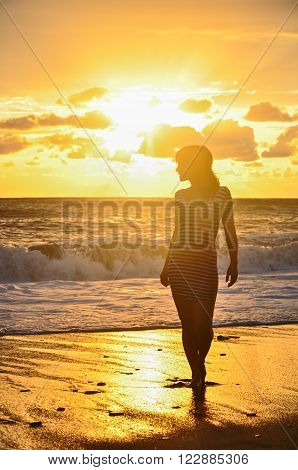 Silhouette of girl in frock standing in sea at golden sunset background