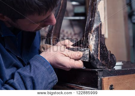 Carpenter Restoring Wooden Furniture With Plaster And Putty Knife