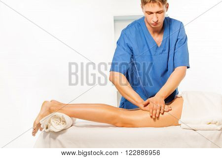 Physical therapist doing massage on woman hip laying on the massage couch