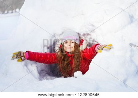 Amusing smiling girl in the winter playing at a snow cave