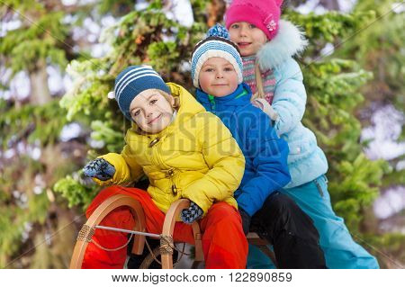 Close portrait of three happy little kids on sledge in the park slide down on snow hill