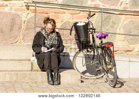 Kalmar Sweden - March 17 2016: A woman sit beside a bike writing in a notepad. She has glasses and a thick coat. Real people in everyday life.