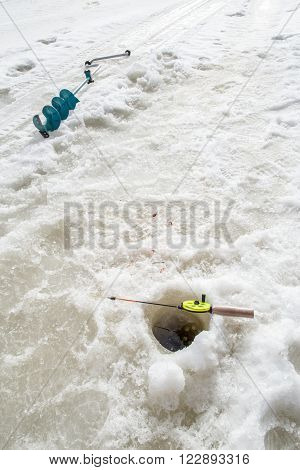 During winter fishing rod lying on the ice near the hole and lies next to borer