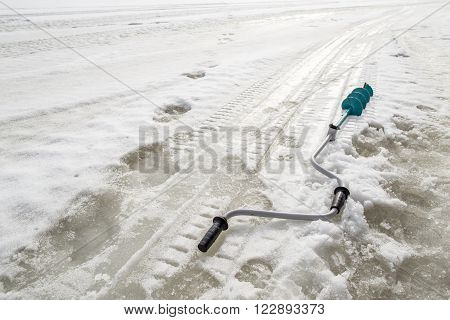 during the winter fishing on the ice borer lies near traces of the legs and snowmobile