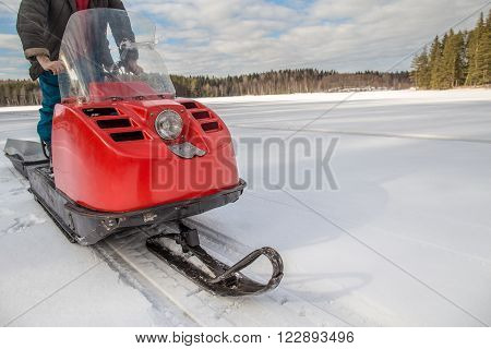 a man riding old red snowmobile on snow-covered lake around a spruce forest