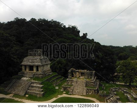 Several Mayan temples as seen from the staircase of a high pyramid at the Palenque archeological site of Chiapas Mexico backed by jungle.